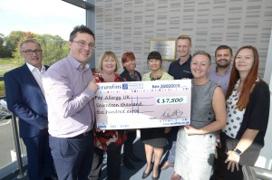 Left, front - Patrick Harte, Eurofins Food Testing General Manager holds the cheque with Carla Jones, Allergy UK CEO
